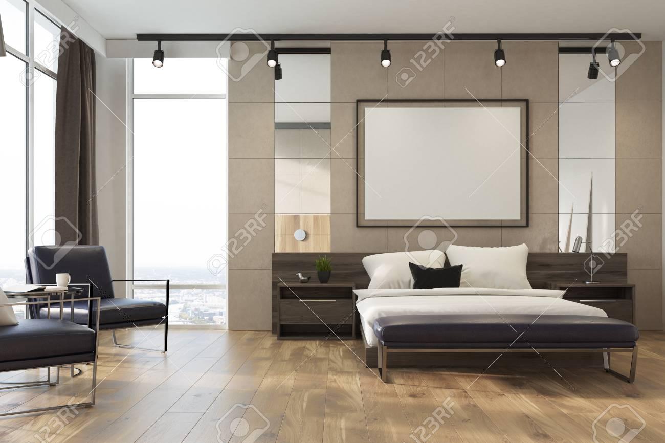 Intérieur de chambre beige avec un lit double, plusieurs tables de chevet,  une affiche encadrée horizontale et de grandes fenêtres avec des rideaux ...