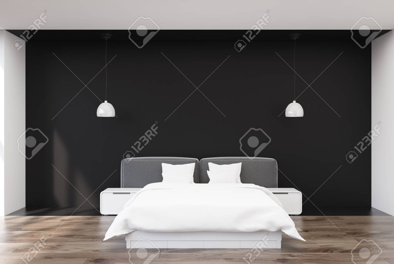 Black bedroom interior with a wooden floor, a double bed with..