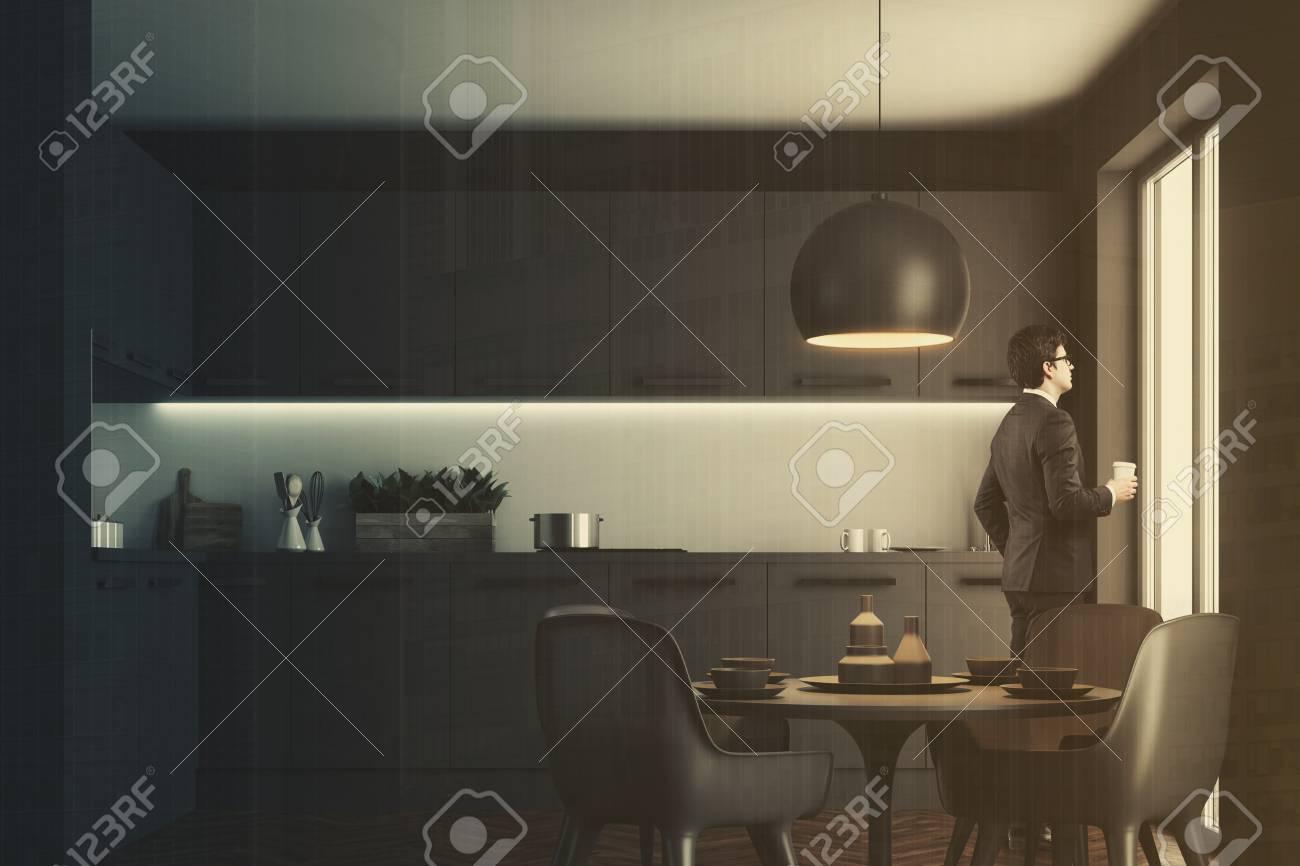 Uomo d affari con caffè in un interno di cucina con pareti nere