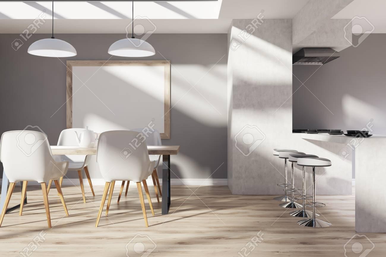 Interior de cocina con paredes grises y de hormigón, una mesa de comedor  con cahirs, un soporte de bar con taburetes, un suelo de madera y un póster  ...