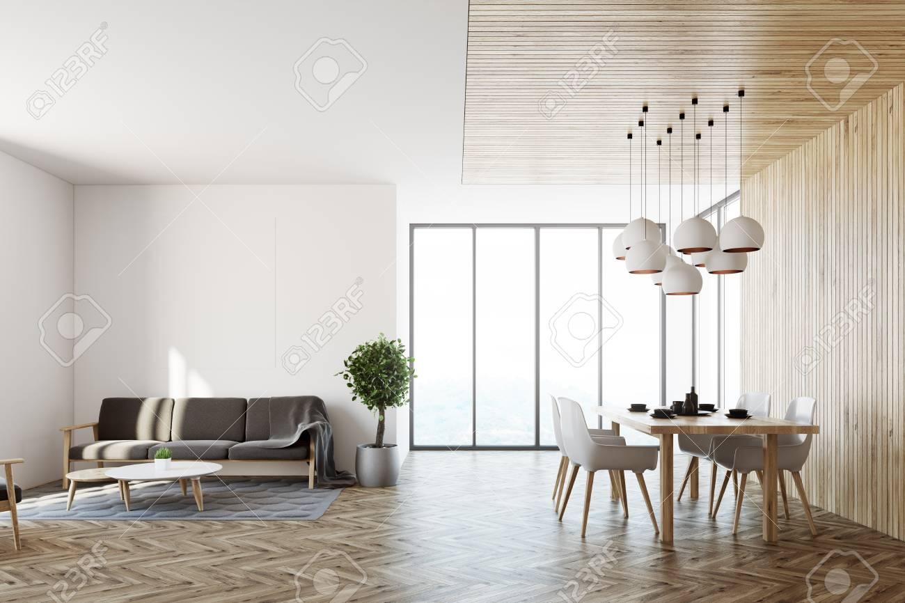 Salle A Manger Gris Blanc Noir intérieur de salon avec des murs blancs, un plancher en bois, un canapé  gris et une table de salle à manger avec des chaises blanches à proximité.