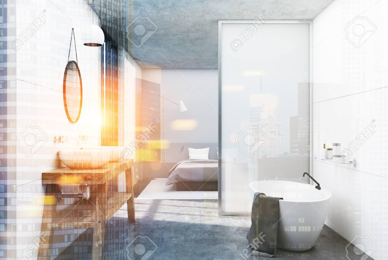 Intérieur de salle de bain blanc avec un sol en béton, une grande fenêtre,  un double lavabo et une baignoire blanche. Une chambre est vue en ...