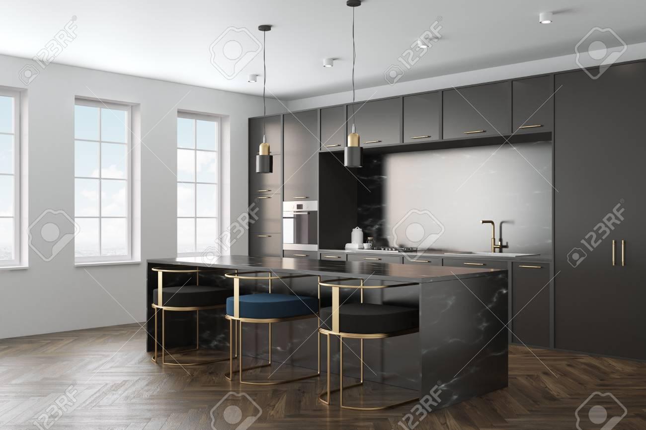 Intérieur de cuisine avec un plancher en bois, des comptoirs en marbre noir  et des armoires noires avec des appareils encastrés. Une barre de marbre ...