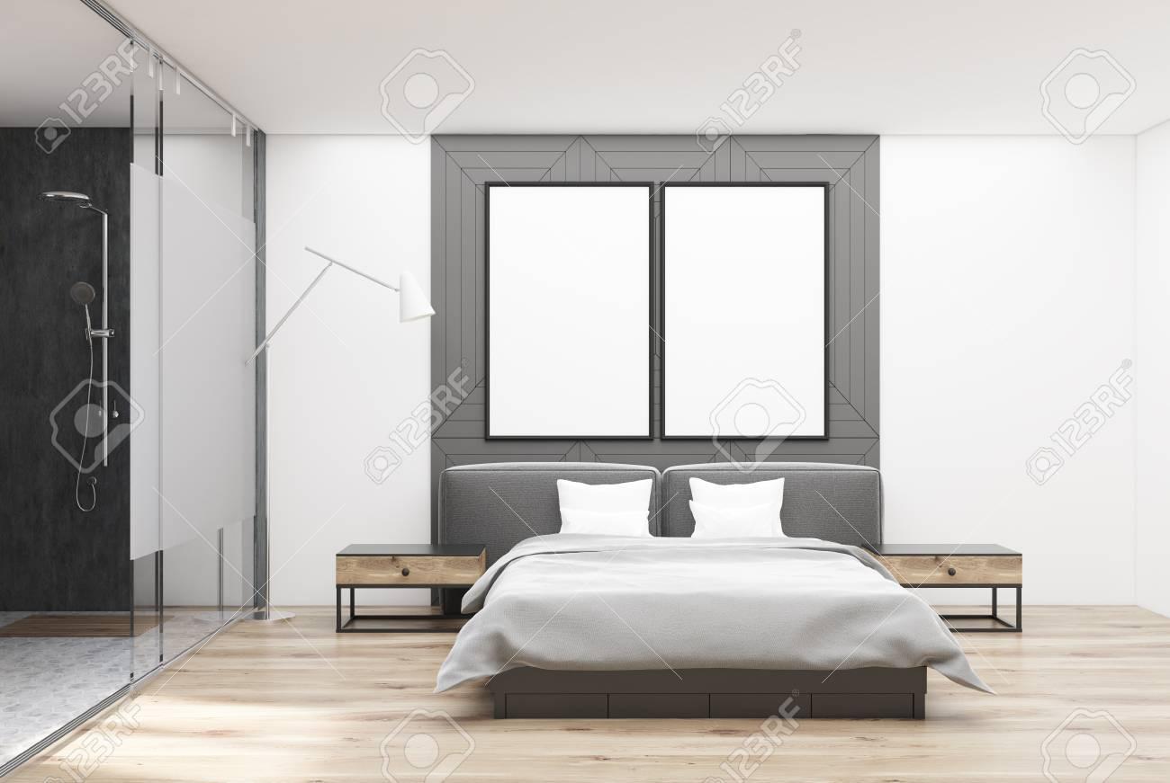 Interno camera da letto con pareti bianche e grigie, pavimento in legno,  letto matrimoniale con rivestimento bianco e due comodini. Due manifesti 3d  ...
