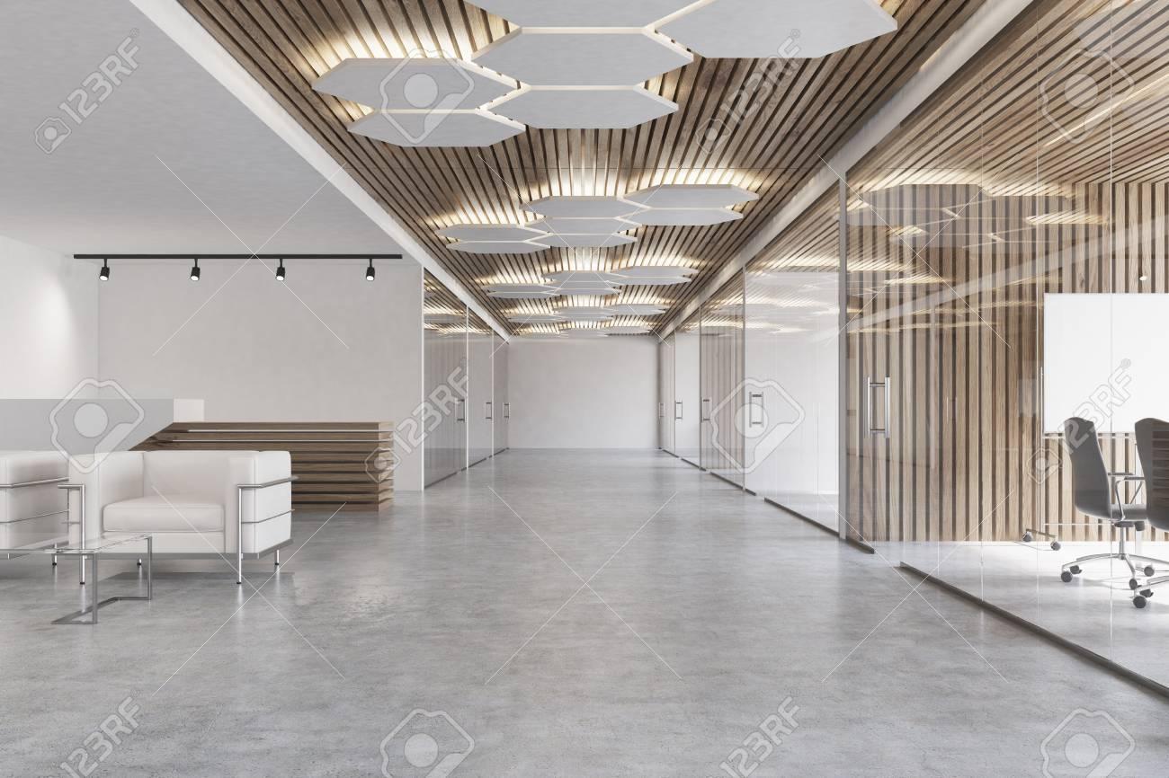 Hall de bureau blanc et bois avec un sol en béton un fauteuil blanc