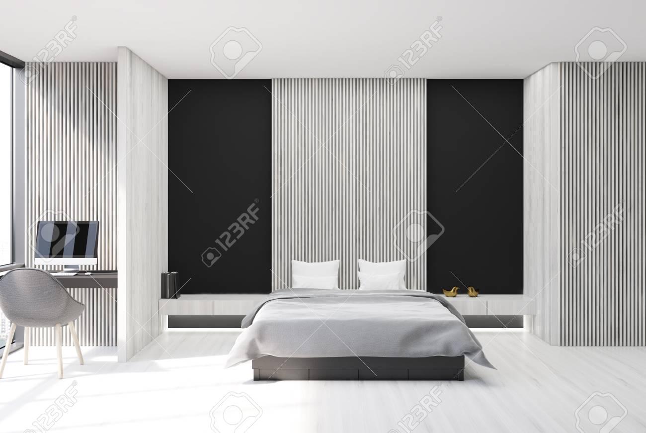 Chambre moderne et intérieur de bureau à la maison avec des murs en bois  noir et blanc, un sol en béton, un lit de maître et un bureau d\'ordinateur.  ...