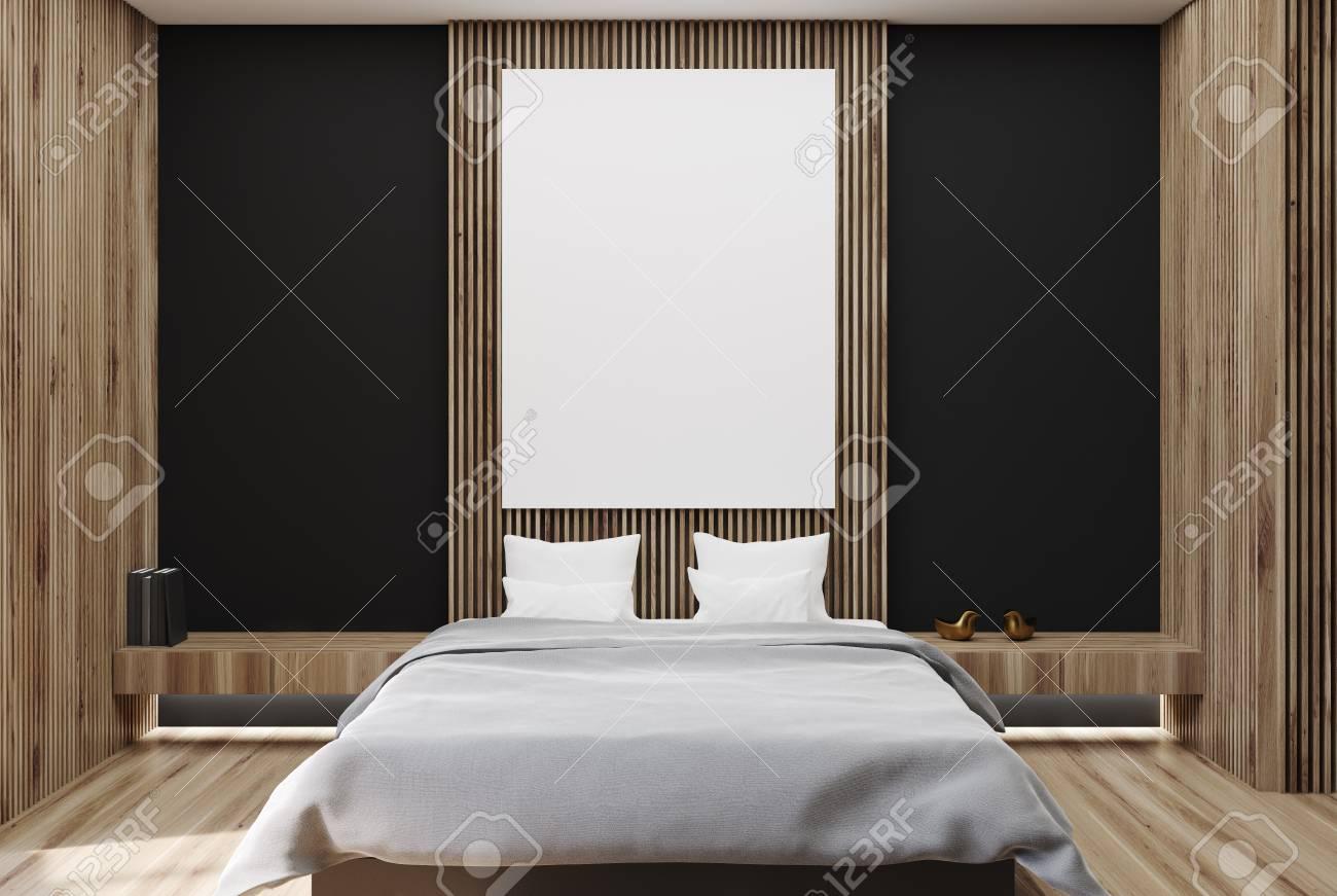 Interno camera da letto moderna con pareti nere e in legno, un pavimento in  legno, una libreria e un letto matrimoniale con un poster verticale ...