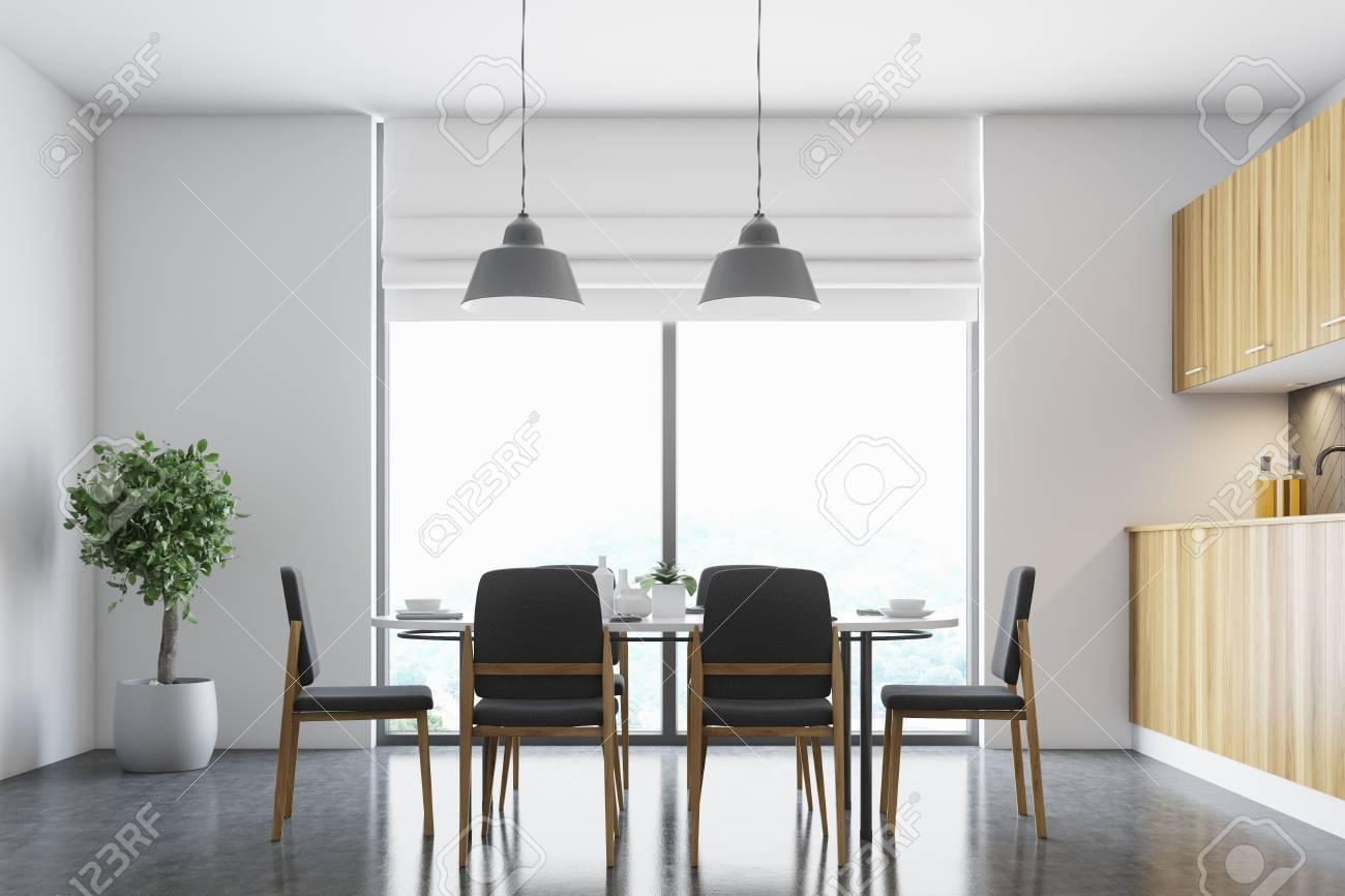 Esquina del comedor blanco con una ventana panorámica, un piso de concreto  y una mesa blanca con sillas negras. Simulacro de representación 3D