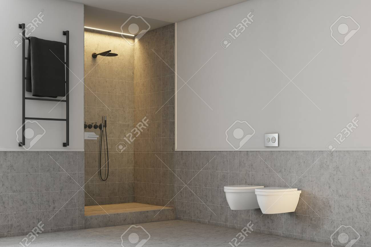 Gray and white bathroom interior with a gray tiled shower stall and two toilets