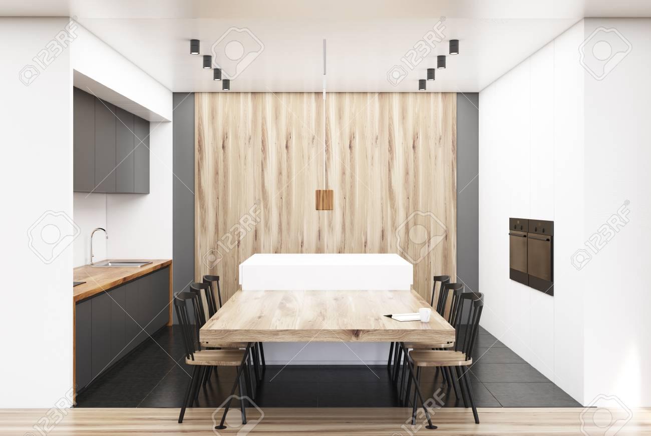 Interior de cocina blanco y madera con una larga mesa de madera con sillas  modernas y encimeras gris y blanco. Simulacro de representación 3D