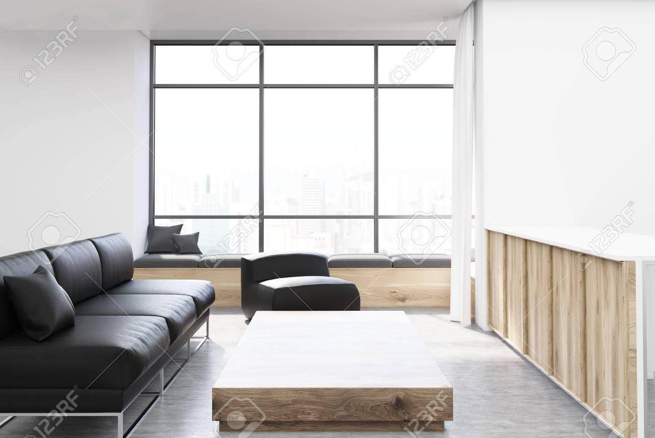 Davanzale Interno Della Finestra interiore bianco e di legno del salone con un sofà nero, un tavolino da  salotto di legno e una poltrona molle vicino ad un davanzale della finestra