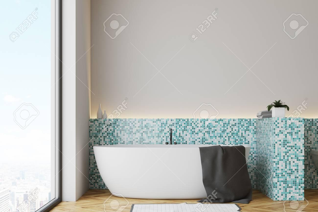 Intérieur de la salle de bain en carrelage vert avec un plancher en bois et  une baignoire blanche avec une serviette suspendue dessus. Rendu 3D, ...