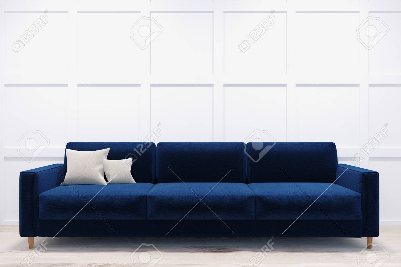 Long and comfortable dark blue sofa standing in a room with white..
