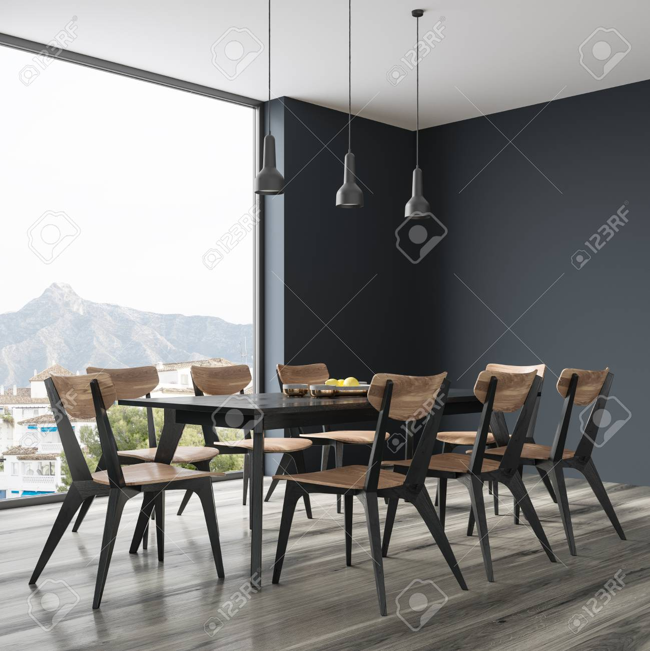 Long black dining room table with black and wooden chairs standing..