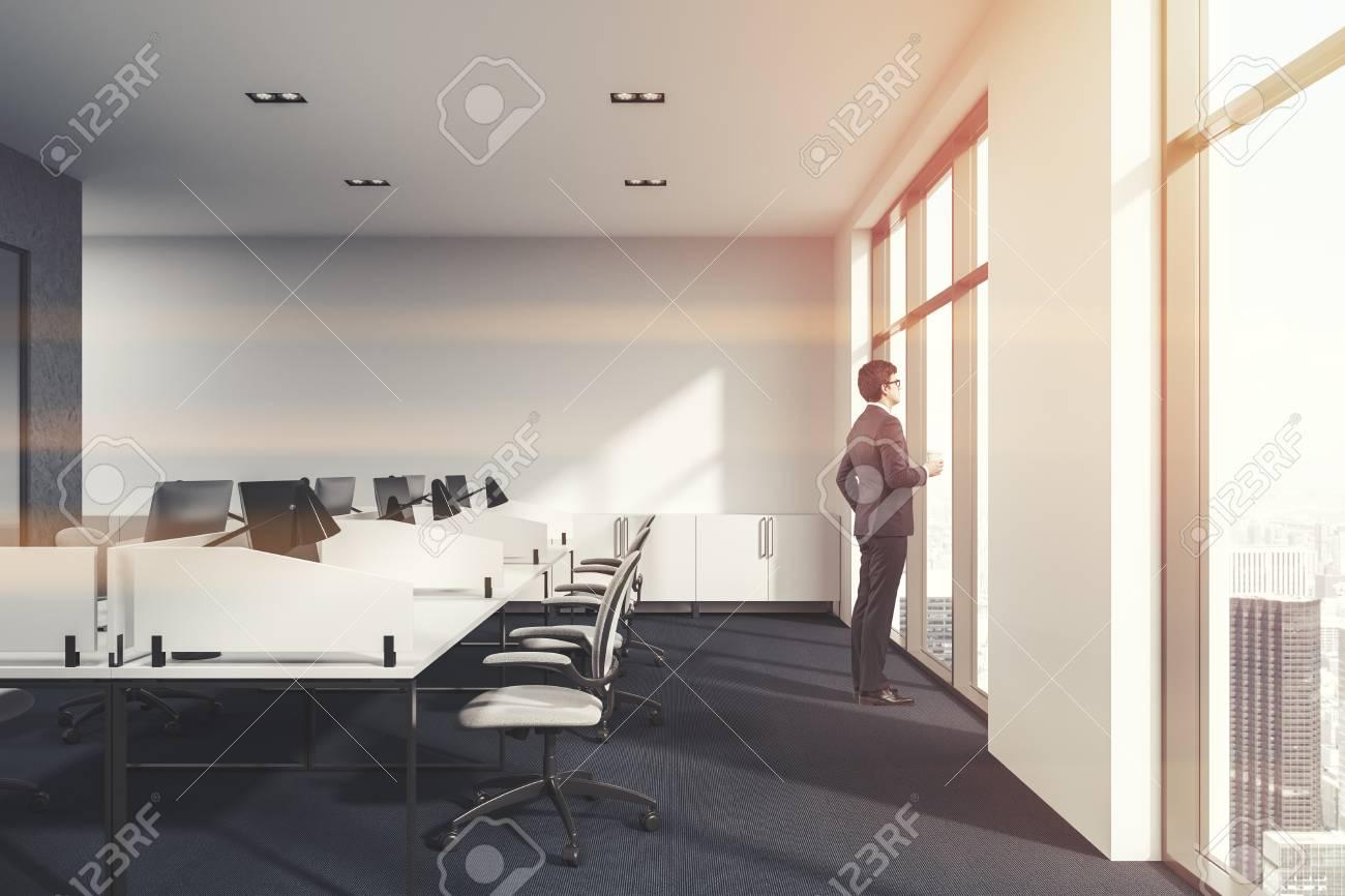 Blanc et chaises de bureau en béton avec des bureaux informatiques