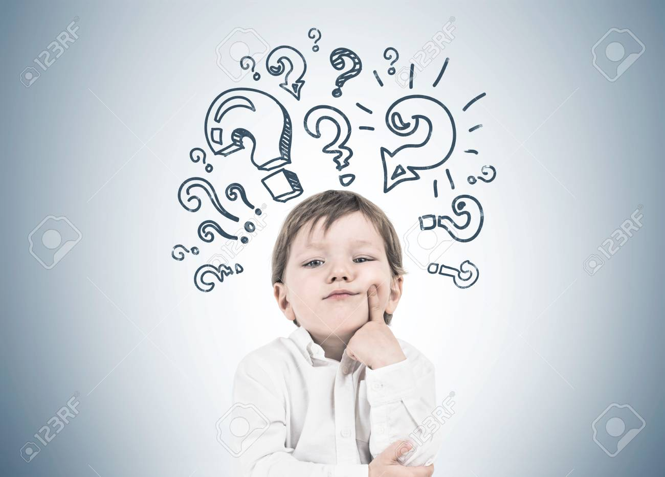 Cute little boy in a white shirt and dark blue jeans is thinking holding his finger near his cheek. Decision making concept. A gray wall background with many question marks - 96979485