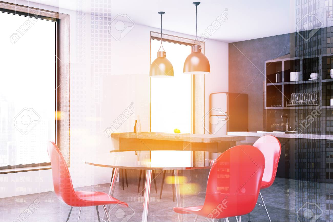 corner of a modern kitchen with a round talbe red chairs large