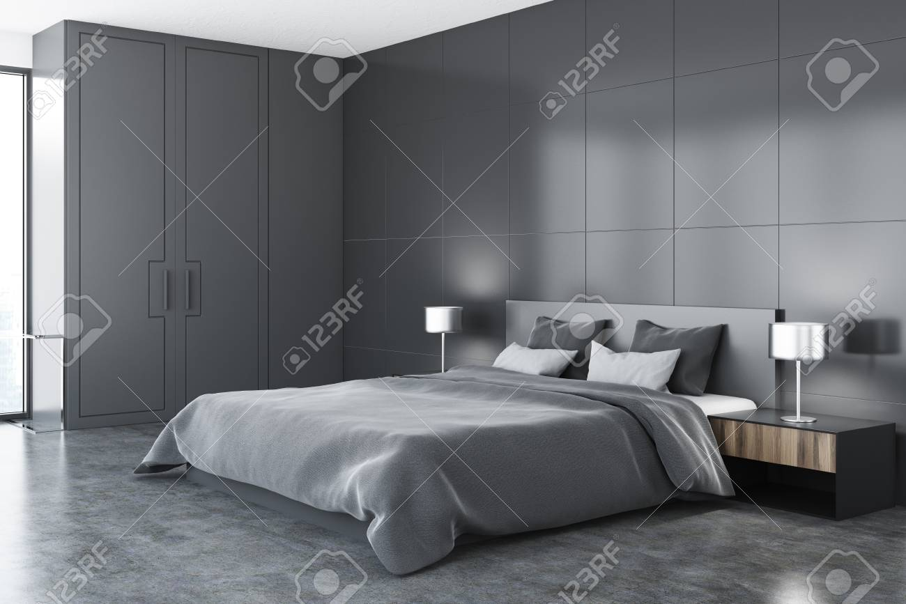 Modern bedroom corner with gray walls, a concrete floor, a master..
