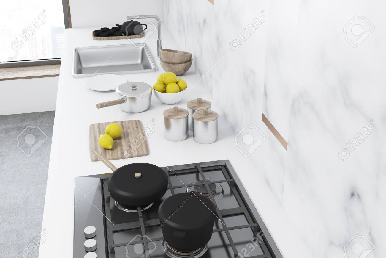 White marble kitchen interior with a white countertop, a stove..