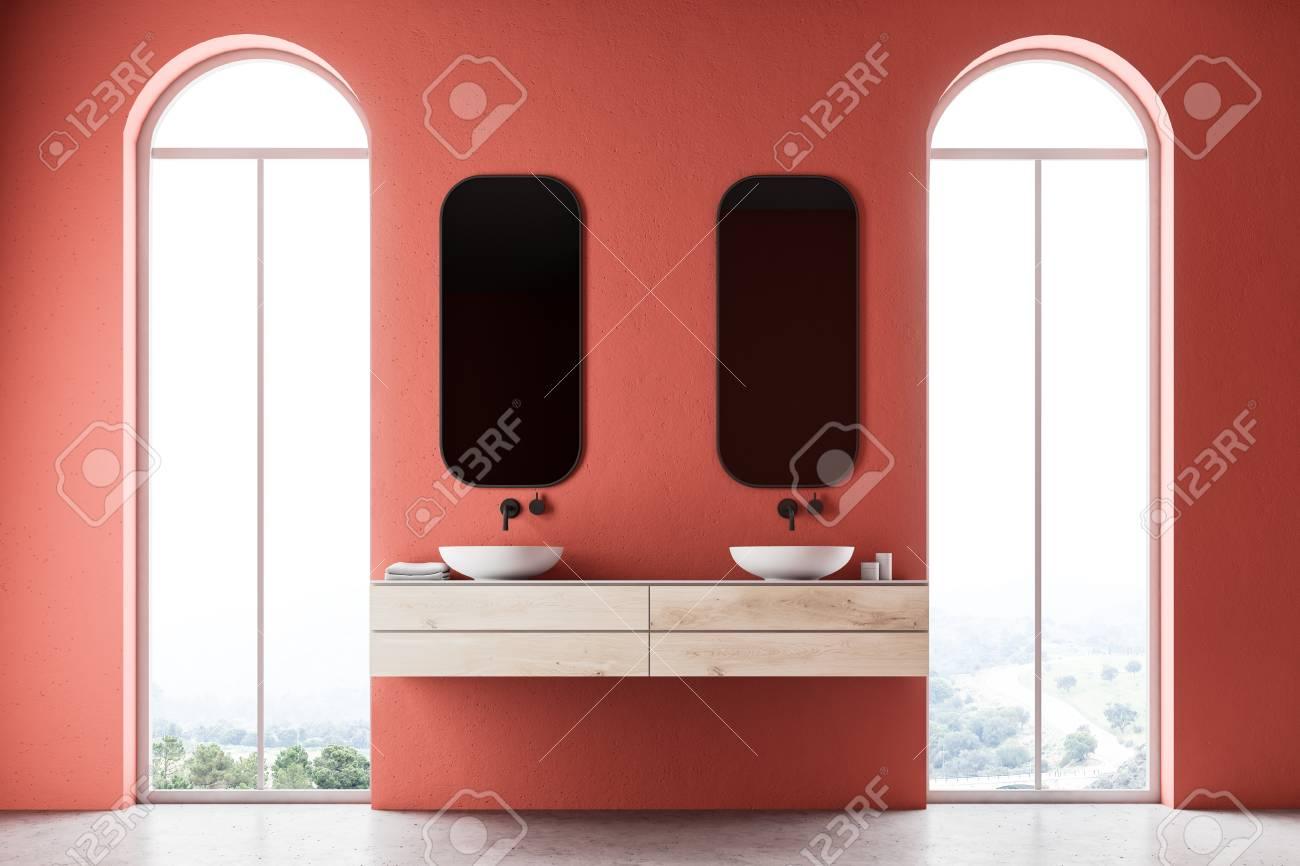 Interior del cuarto de baño rojo minimalista con un fregadero doble con dos  espejos ubicados entre dos ventanas de espejo 3d representación