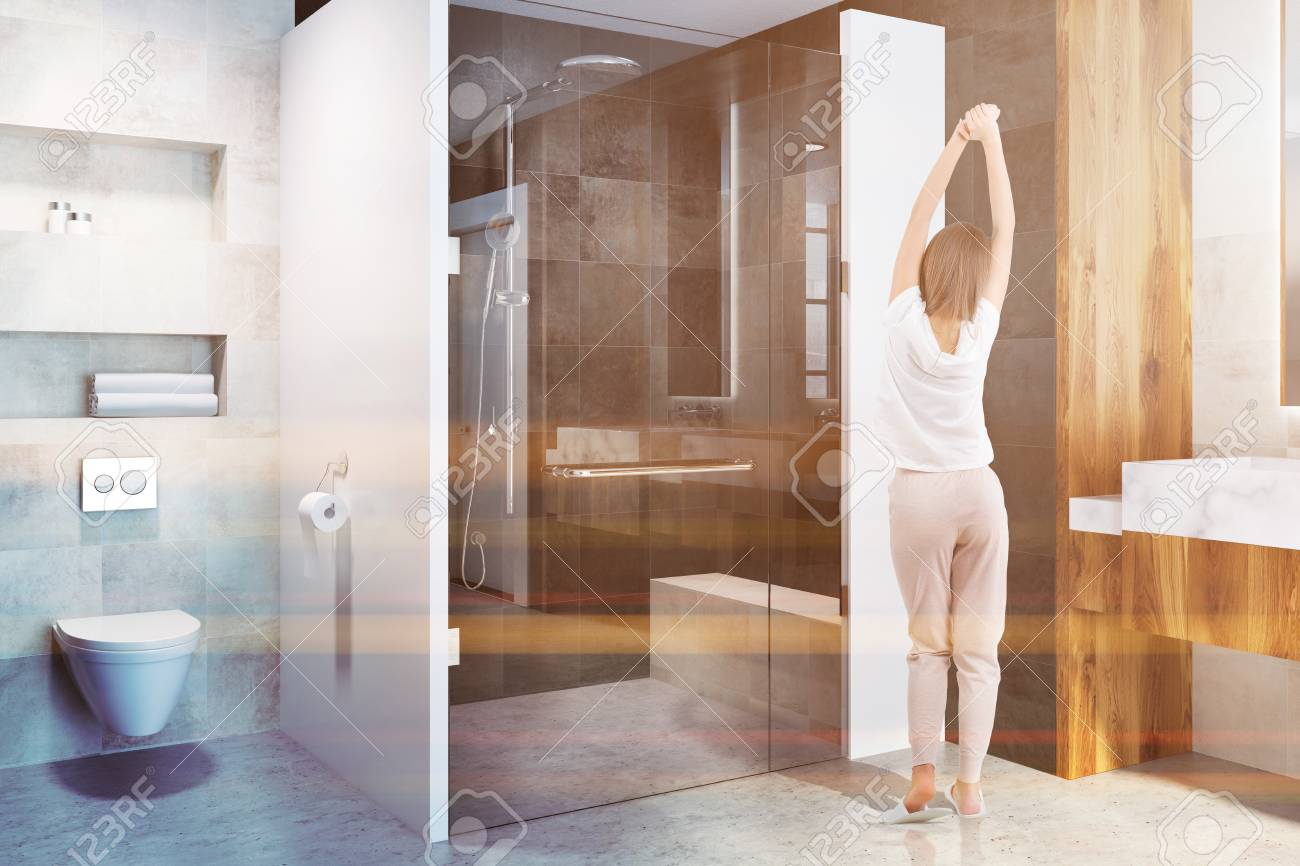 . Glass door shower stall in a modern bathroom interior with white