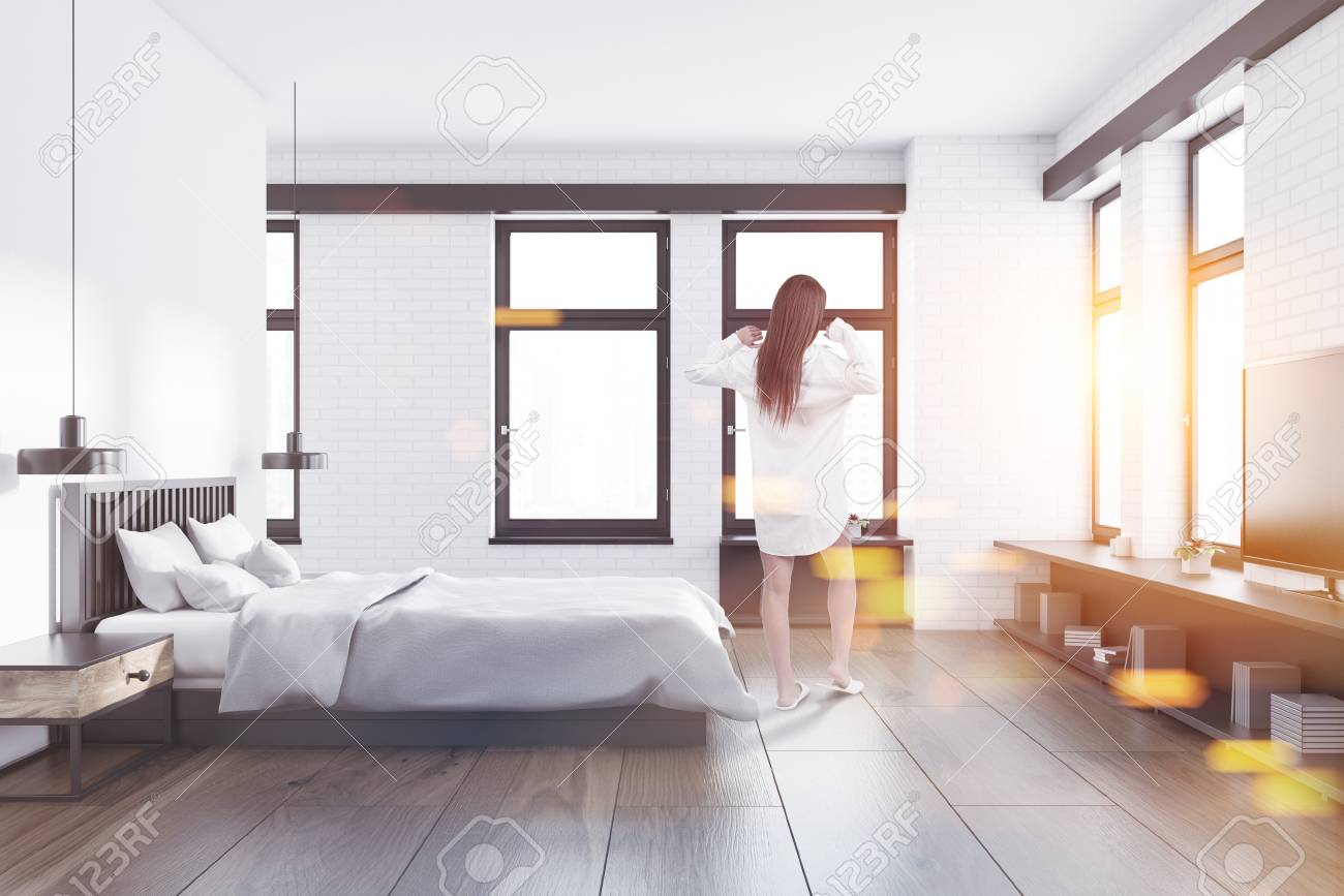 Woman In A Bedroom Interior With White And White Brick Walls