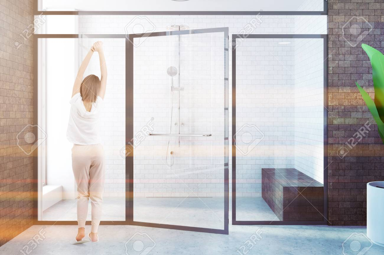Woman Standing Near A Modern Shower Stall With Brick Walls And