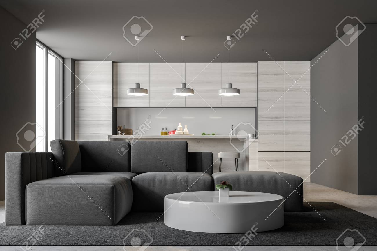 Banque dimages gray kitchen interior with a bar and loft windows a living room with a gray sofa and a round coffee table in the foreground