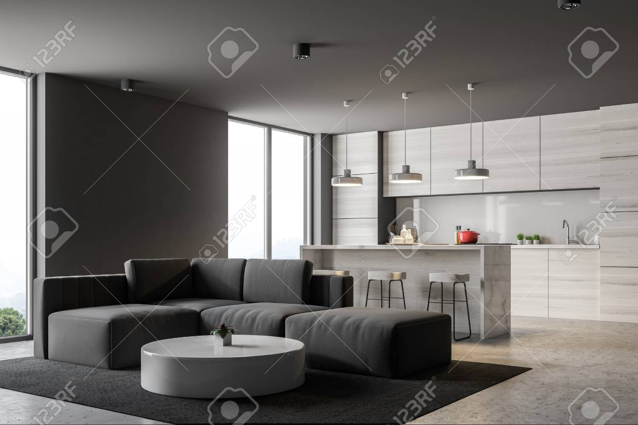 Banque dimages gray kitchen corner with a bar and loft windows a living room with a gray sofa and a round coffee table in the foreground