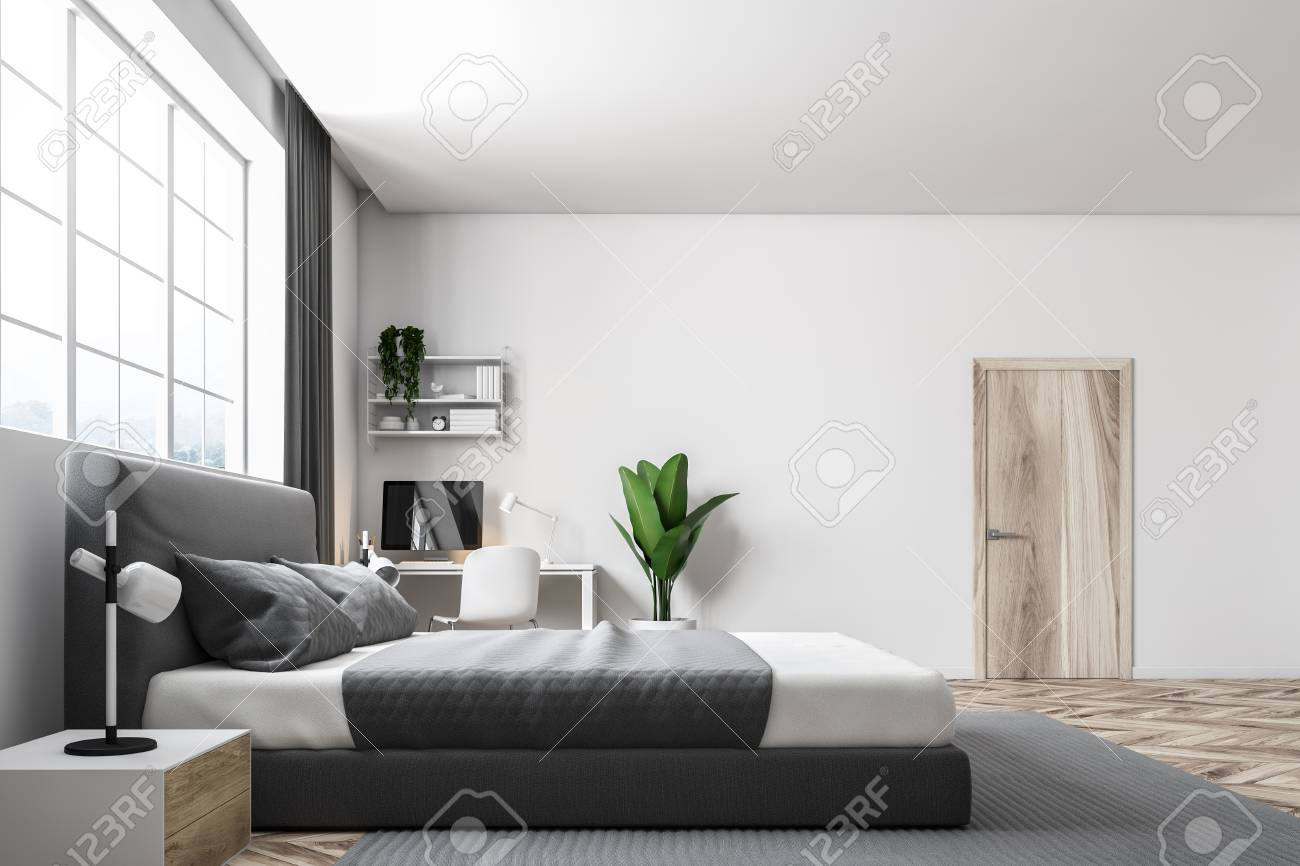 Side View Of A Master Bedroom With White Walls A Carpet On A