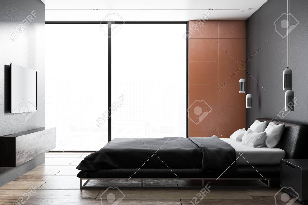 Modern bedroom interior with orang tile walls, a wooden floor,..