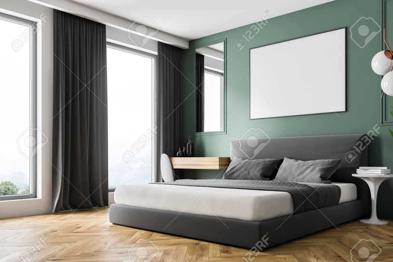 Corner of modern bedroom with green walls, wooden floor, gray..