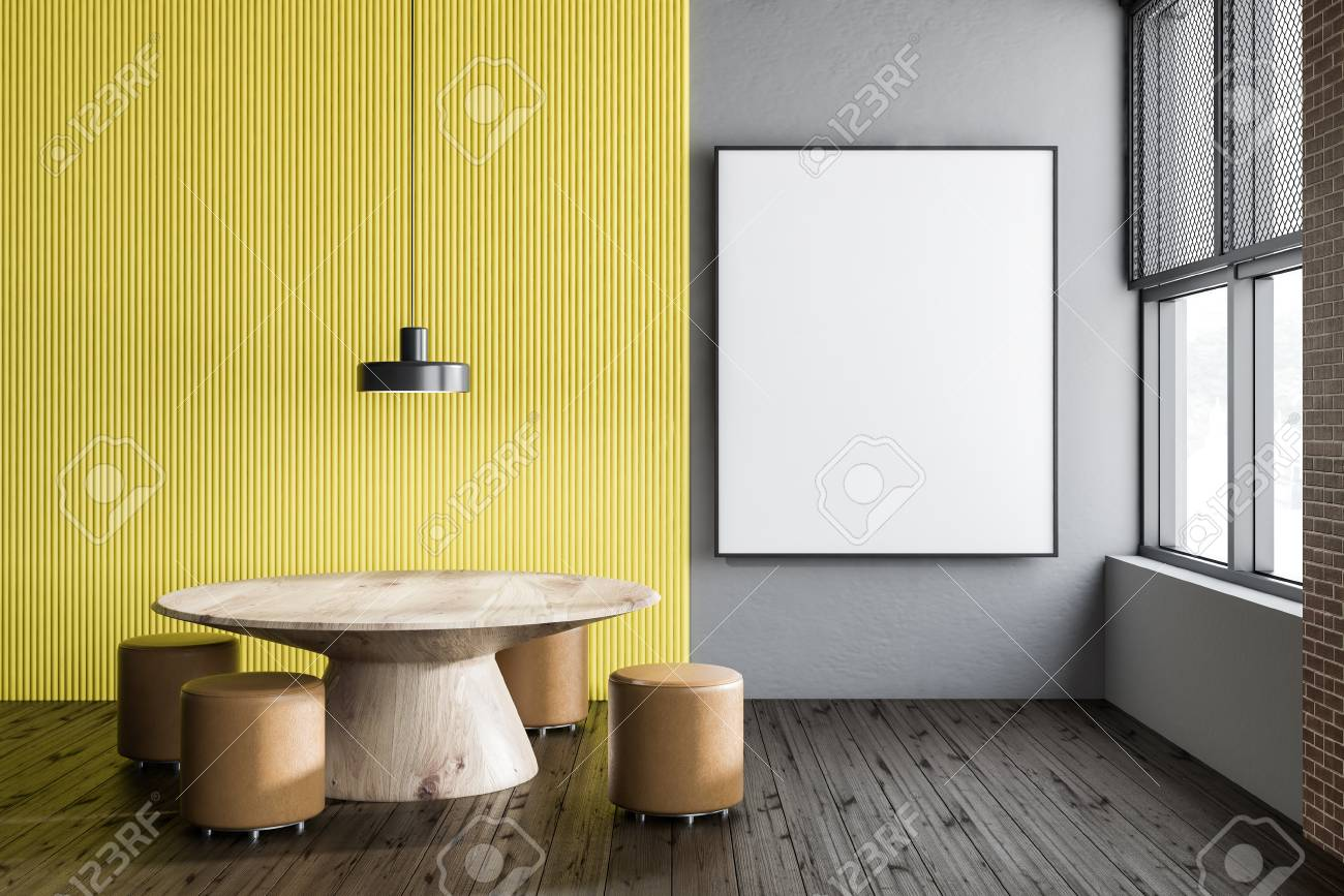Interior of dining room with gray and yellow walls, wooden floor..