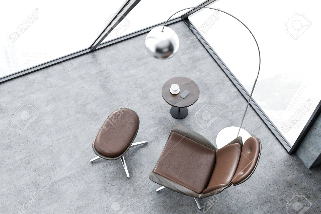 Top view of brown armchair standing in office lounge with concrete..