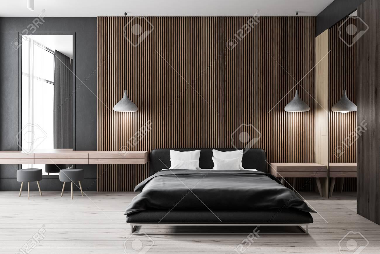 Interior of modern bedroom with dark wooden walls, wooden floor,..