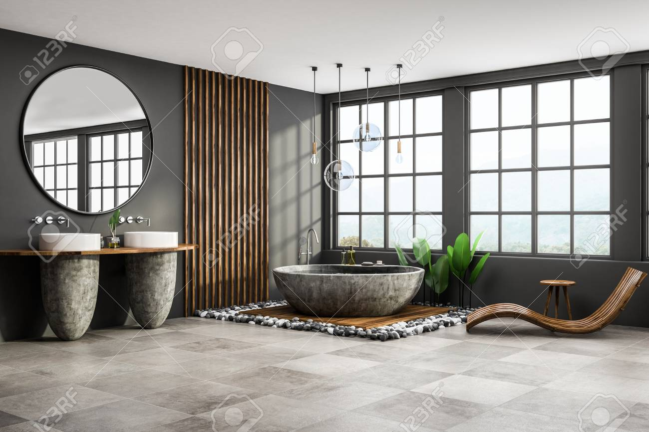 Corner of modern bathroom with gray and wooden walls, tiled floor, round gray bathtub, two white sinks with big round mirror and wooden armchair. 3d rendering - 112602561