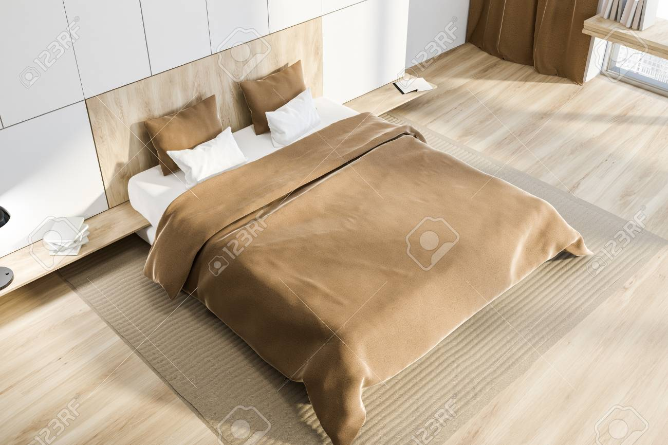 Stock Photo - Top view of master bedroom with white walls, wooden floor, gray carpet and white and wooden bed with beige blanket. 3d rendering