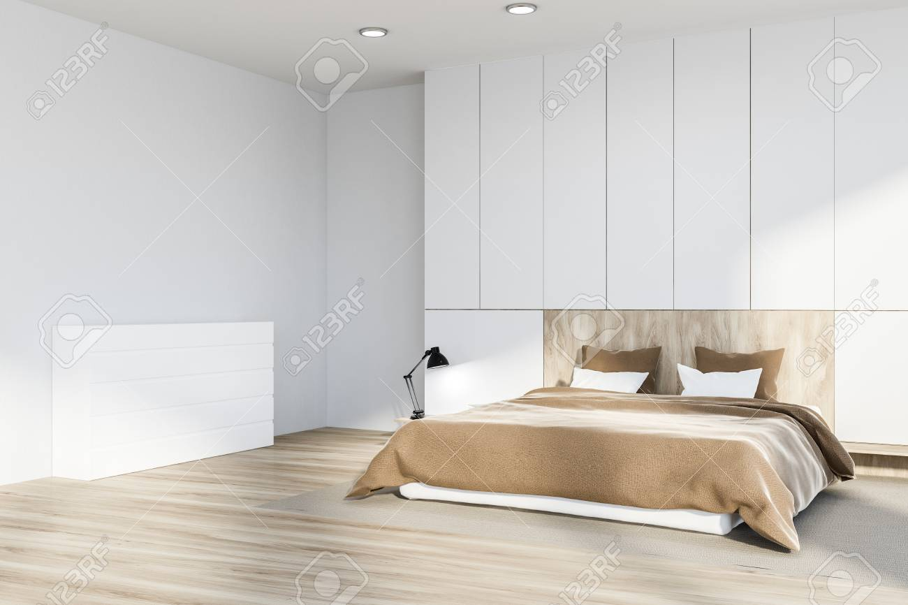 Corner of master bedroom with white walls, wooden floor with..