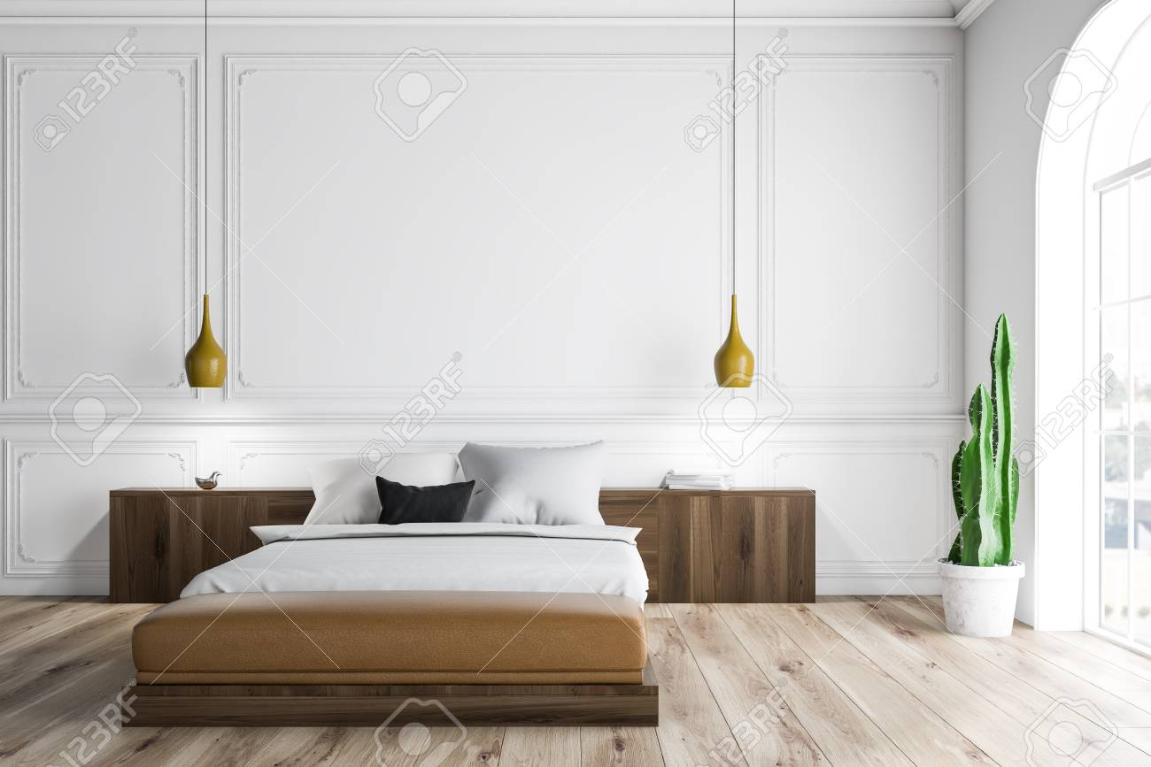 Interior of bedroom with white walls, wooden floor, arched windows,..
