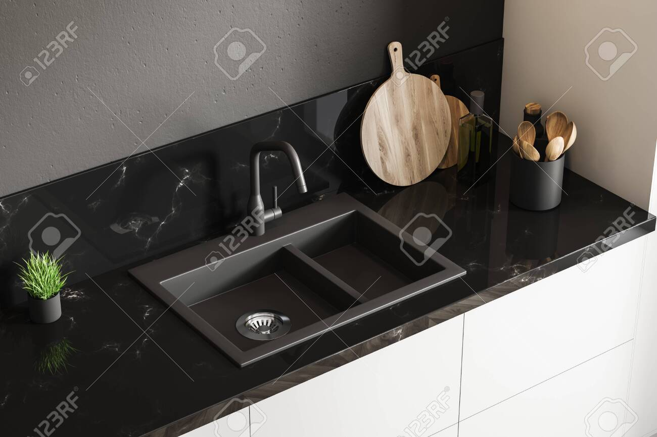 Top view of black marble kitchen sink standing on white countertop..