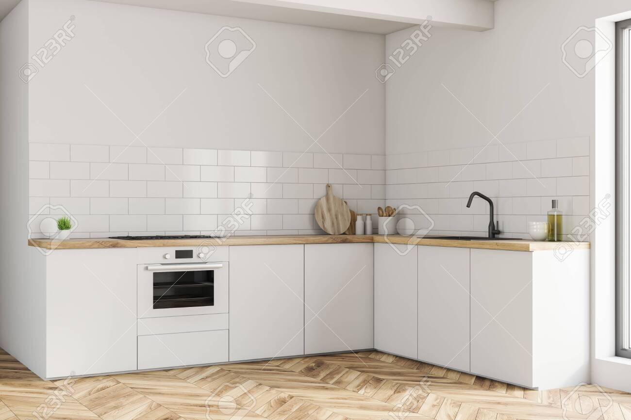 Corner of small kitchen with white walls, wooden floor and white..