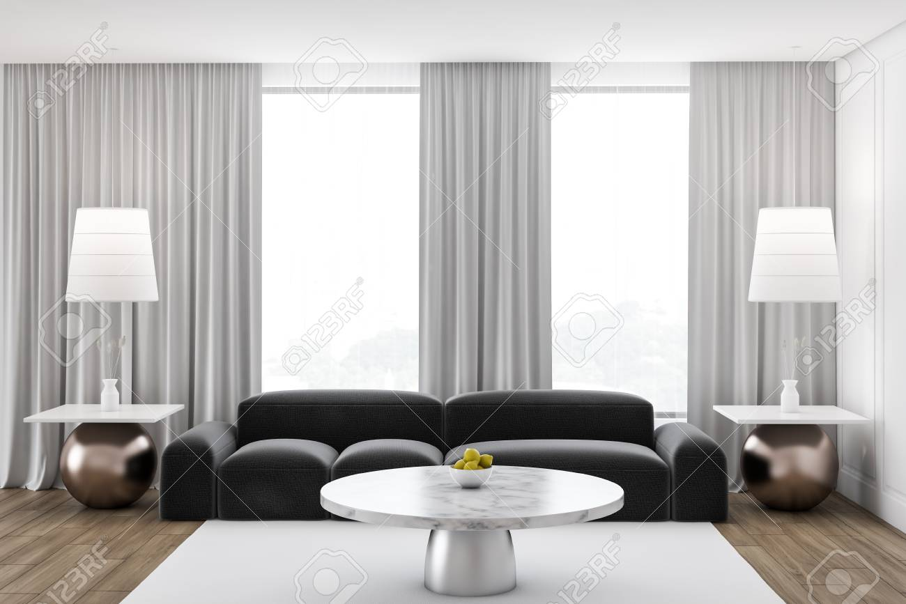 Interior of stylish living room with white walls, large windows..