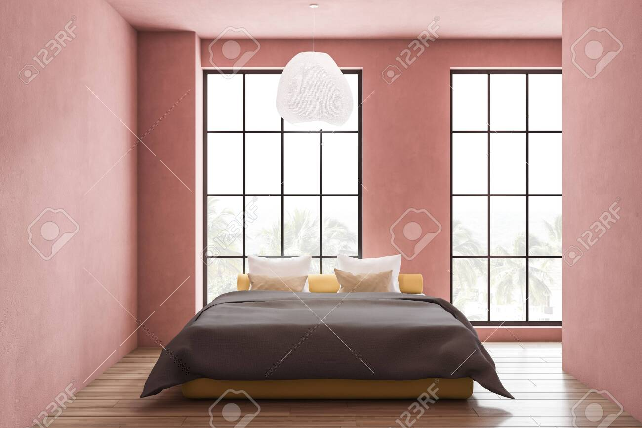 Interior of stylish bedroom with pink walls, wooden floor, large..
