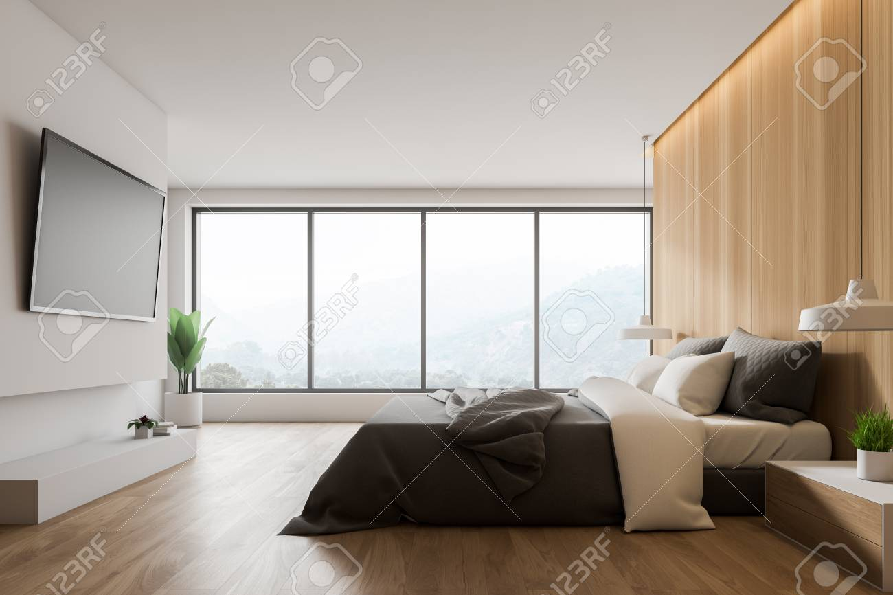 Interior of master bedroom with large window, wooden and white..