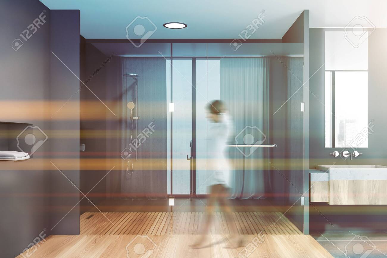 Young Woman Walking In Modern Bathroom With Gray Walls Wooden