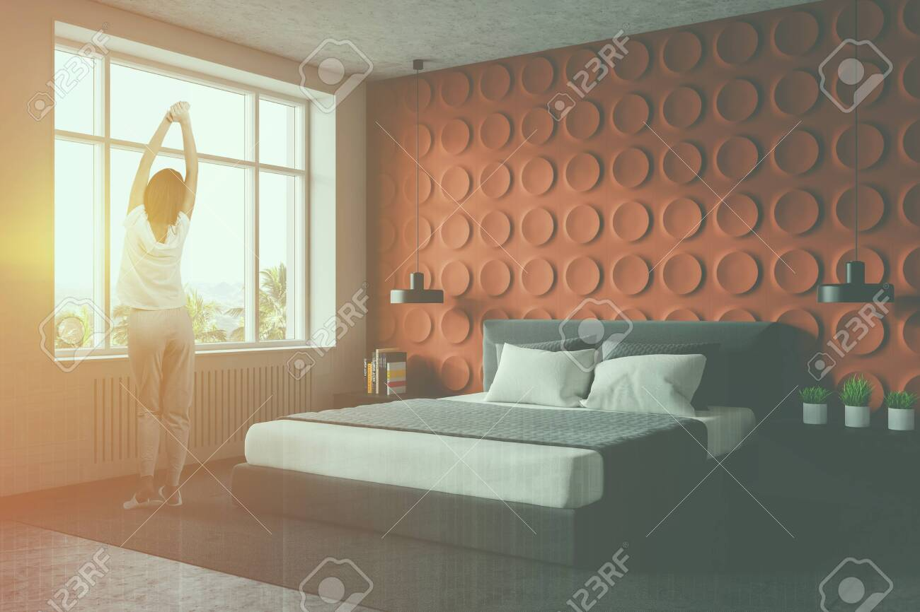 Woman standing in modern bedroom with orange and white walls,..