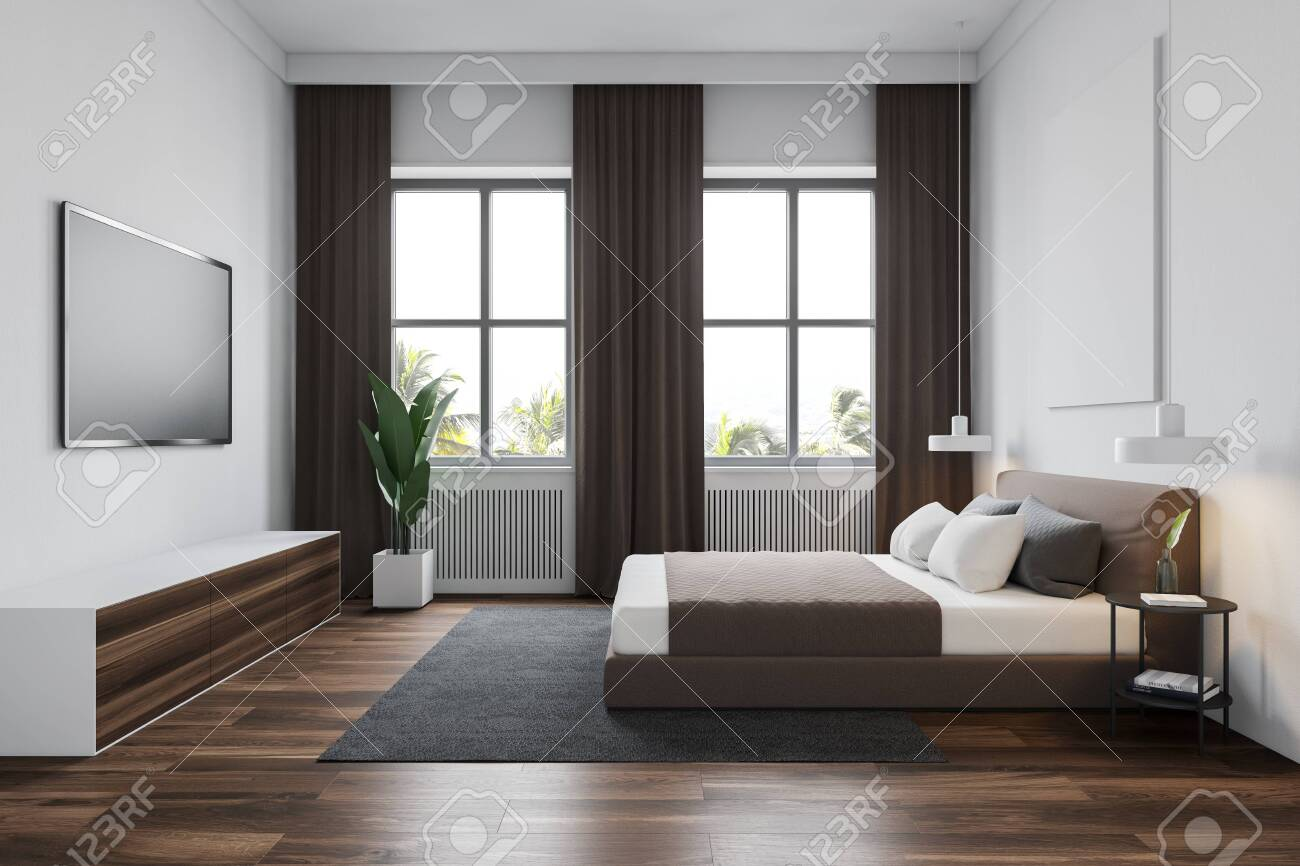 Side view of modern bedroom with white walls, wooden floor with..