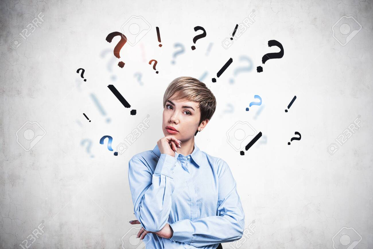 Beautiful thoughtful young businesswoman standing near concrete wall with question and exclamation marks drawn on it. Concept of choice and decision making - 133137717