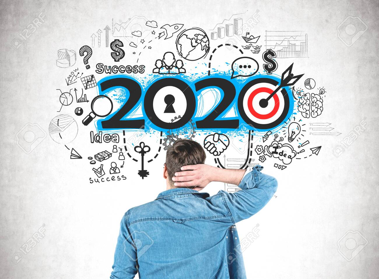 Rear view of confused young man in jeans shirt looking at 2020 strategy sketch drawn on concrete wall. Concept of planning and new year resolutions - 133308502