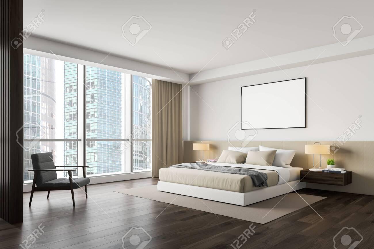 Corner of master bedroom with white walls, dark wooden floor,..